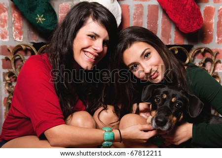 Pretty young brunette women in a home lifestyle pose with a dog next to a red brick fireplace with hanging holiday stockings. - stock photo