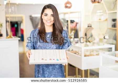 Pretty young brunette working at a jewelry shop and showing some necklaces with a smile