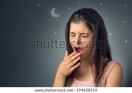 Pretty young brunette yawning with her hand over her mouth - stock photo