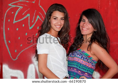 Pretty young brunettes in an outdoor lifestyle fashion pose with a red background.