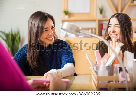 Pretty young brunettes laughing and having a good time together while getting their nails done at a beauty salon - stock photo