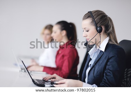 Pretty young business woman group with headphones smiling at you against white background