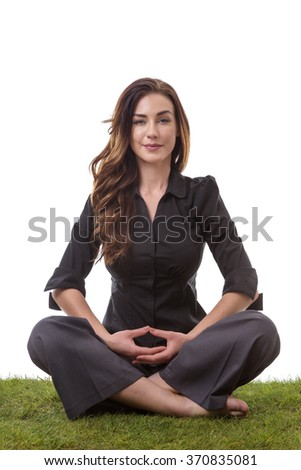 Pretty young business woman in a suit, sitting on grass in a crossed legs yoga pose, with her arms on her lap - stock photo