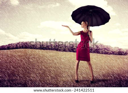 Pretty young business woman standing with umbrella in the rain. Concept of crisis protection and risk insurance.  - stock photo