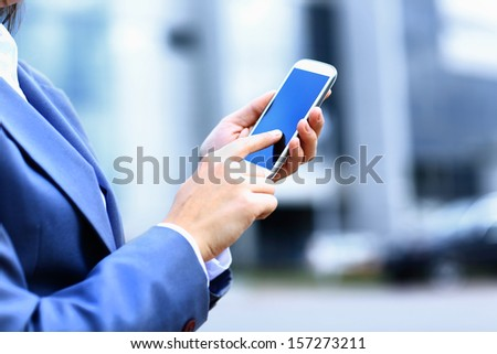 Pretty young business woman using mobile phone outdoor - stock photo