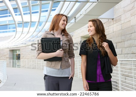 Pretty young business women walking outside office building - stock photo