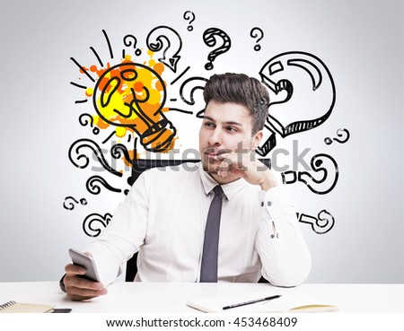 Pretty young businessman in white shirt and grey tie thinking about something in front of wall with sketch of question marks and lightbulb. Concetpt of thinking - stock photo