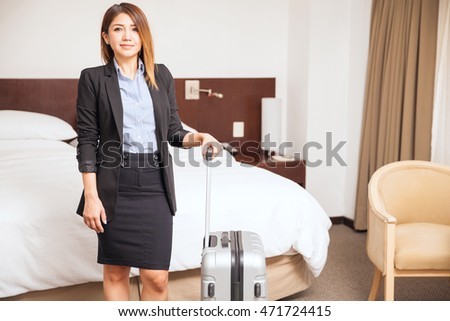 Pretty young businesswoman holding a suitcase and standing in a hotel room during a business trip