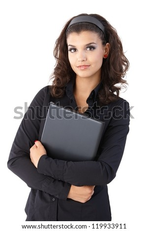 Pretty young businesswoman holding laptop, looking at camera. - stock photo
