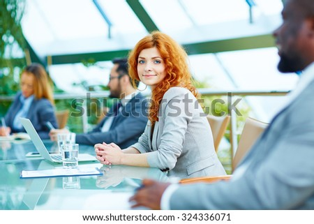 Pretty young businesswoman looking at camera during lecture - stock photo