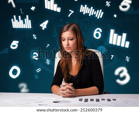 Pretty young businesswoman sitting at desk with diagrams and statistics - stock photo
