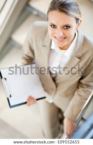 pretty young businesswoman standing on stairs and looking up - stock photo