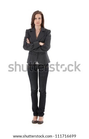 Pretty young businesswoman standing with arms folded, looking at camera, isolated on white, full length. - stock photo