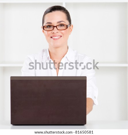 pretty young businesswoman using laptop in office - stock photo