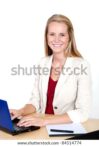 Pretty young businesswoman with laptop computer at desk smiling