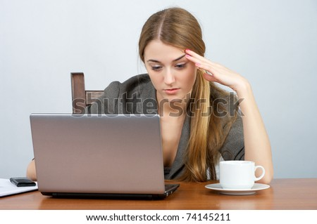 Pretty young businesswoman working on laptop in the office - stock photo