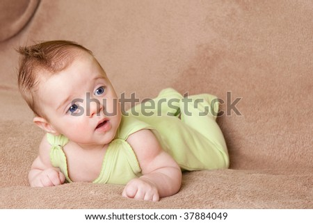 pretty young caucasian baby lying on brown towel and looking away from camera