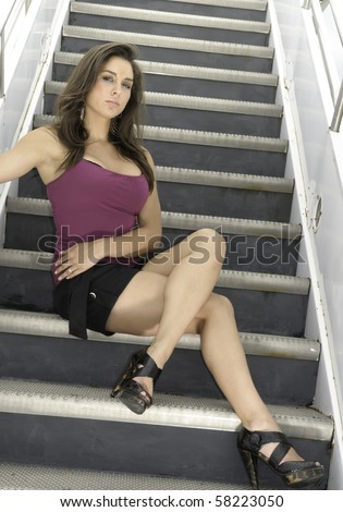Pretty young Caucasian brunette sits near bottom of mobile stairs at airport