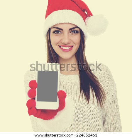 Pretty young Caucasian brunette woman with knitted Santa hat showing smartphone. Closeup of beautiful Christmas girl with smart phone. Square image - stock photo