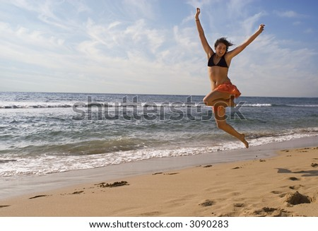 pretty young caucasian girl is jumping up in  the air at the beach in Hawaii