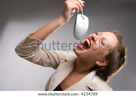 Pretty young caucasian girl pretending to eating computer mouse - stock photo