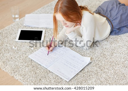 Pretty young Caucasian woman lying on the floor and making notes in copybook. Redhead student girl using electronic tablet computer with blank copy space screen for your text or promotional content  - stock photo