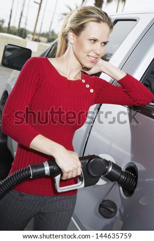 Pretty young Caucasian woman refueling her car at the gas station