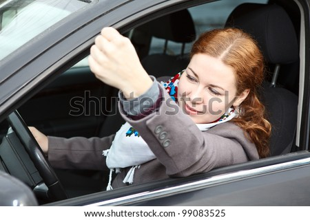 Pretty young Caucasian woman shaking hers fist sitting in car