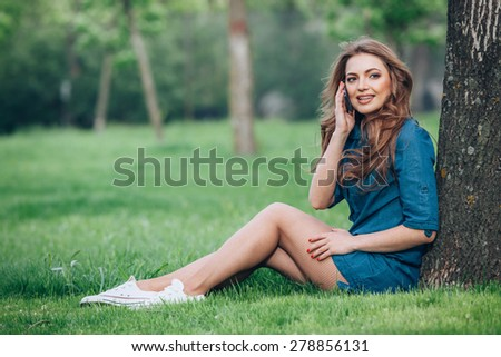 Pretty young caucasian woman  sitting outside under a tree talking on a smartphone device. Filtered effects