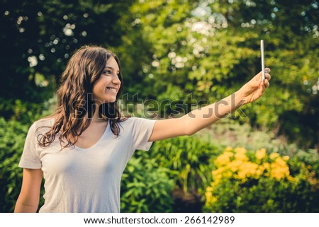 Pretty young caucasian woman smiling cheerfully for a selfie on her smartphone. Green natural environment in background. Filtered effects. - stock photo