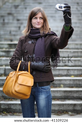 Pretty young caucasian woman taking a self-portrait while outdoors - stock photo