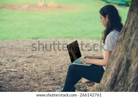 Pretty young caucasian woman wearing black jeans sitting outside under a tree working on a laptop computer. Filtered effects - stock photo