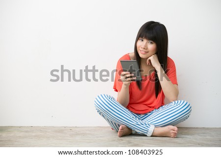 Pretty young Chinese woman sitting on the floor with a e-book reader . - stock photo