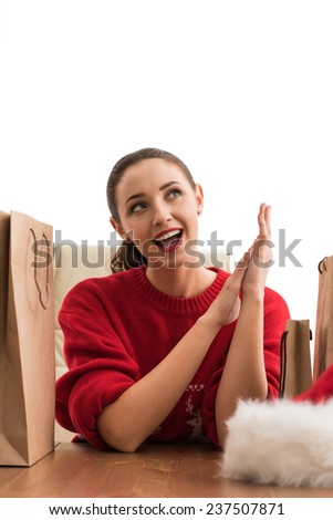 Pretty young Christmas woman sitting at office with shopping bags and laughing - stock photo