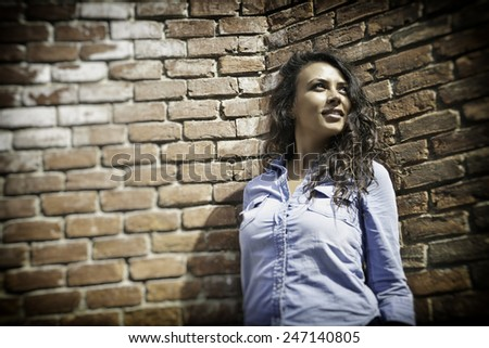 Pretty young city girl standing against an exterior brick wall.