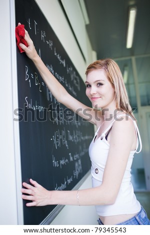 pretty, young college student erasing the chalkboard/blackboard during a math class (color toned image; shallow DOF) - stock photo