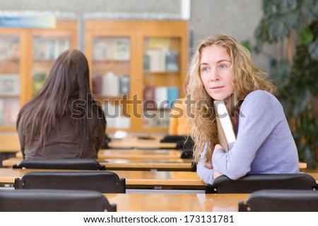 pretty young college student in a library. looking away - stock photo