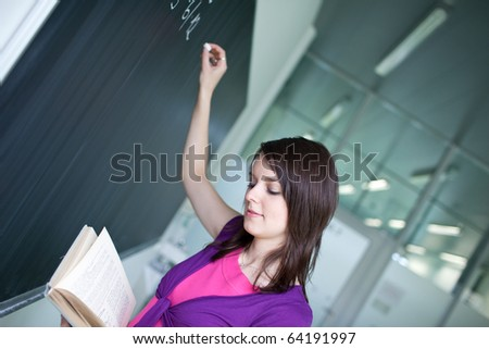 pretty young college student or teacher writing on the chalkboard/blackboard during a math class (shallow DOF; color toned image) - stock photo