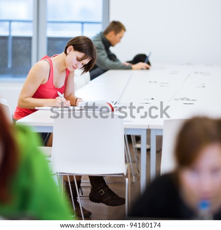 Pretty young college student studying in the library/a study room at campus (shallow DOF) - stock photo