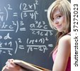 pretty young college student writing on the chalkboard/blackboard during a math class - stock photo