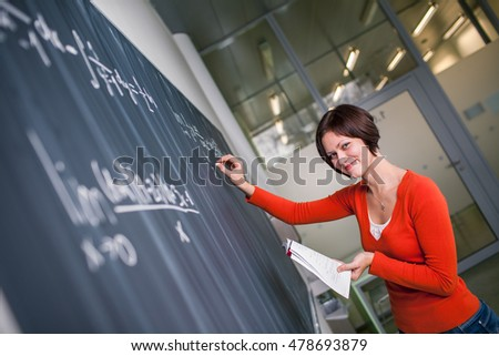 Pretty, young college student writing on the chalkboard/blackboard during a math class (color toned image)