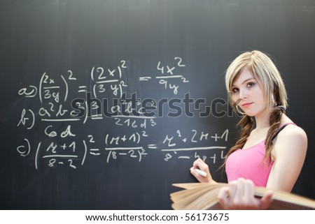 pretty young college student writing on the chalkboard/blackboard during a math class (color toned image) - stock photo