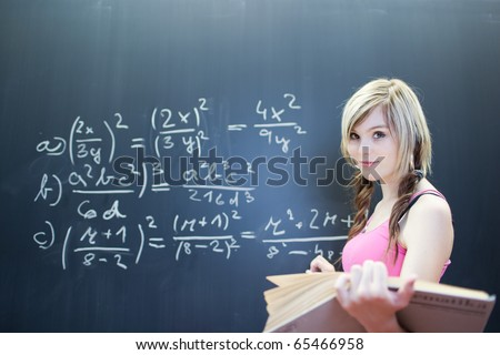 pretty young college student writing on the chalkboard/blackboard during a math class (shallow DOF; color toned image)