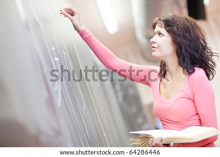 pretty young college student/young teacher writing/drawing on the chalkboard/blackboard during chemistry class (shallow DOF; color toned image) - stock photo