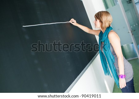 pretty young college student/young teacher writing on the chalkboard/blackboard during a math class (color toned image; shallow DOF) - stock photo