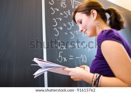 pretty young college student/young teacher writing on the chalkboard/blackboard during a math class - stock photo