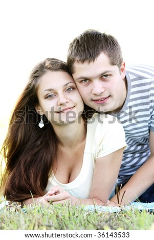 Pretty young couple laying down on grass photo with copy-space above