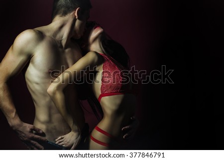 Pretty young couple of undressed sensual woman with beautiful straight body in red lace erotic lingerie with muscular man posing indoor on dark purple background, horizontal picture - stock photo