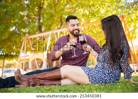 Pretty young couple toasting with wine while having a picnic at a park - stock photo