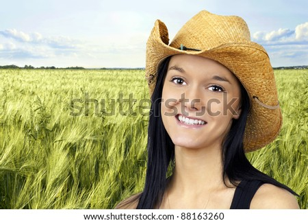 Pretty young cowgirl wearing a straw cowboy hat smiling - stock photo